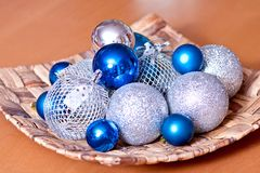 Shiny blue and silver baubles in a bowl. Various sizes blue and silver Christmas plastic baubles in a weaved basket Stock Photos