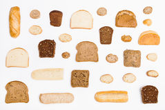 Various sliced bread loaves and rolls on white stock photography