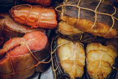 Various smoked fish tied with a tourniquet, prepared tasty seafood background. Toned Stock Photos