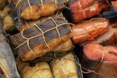 Various smoked fish tied with a tourniquet, prepared tasty seafood background. Toned Royalty Free Stock Images
