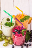 Various smoothies in glasses. Smoothies in glasses of different fruits on a wooden table Royalty Free Stock Image