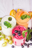 Various smoothies in glasses. Smoothies in glasses of different fruits on a wooden table Royalty Free Stock Images