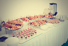Various snacks on banquet table, toned Stock Photos