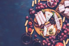 Various snacks-fruit, cheese,sausage, red wine. Top view, copy space. Toned photo. royalty free stock photography