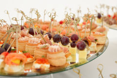 Various snacks in plate on banquet table Royalty Free Stock Photo