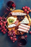 Various snacks on a wooden board, fruits, cold meat, sausage, cheese, dates, olives, jerky. Red wine in glasses and appetizer on a royalty free stock images
