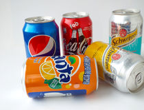 Various soda drinks in aluminum cans, fanta, coca-cola, pepsi and schweppes Stock Photos