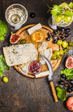 Various soft cheeses light and dark grapes on a cutting board with a knife for cheese peach wine glasses on wooden rustic backgrou Stock Photos