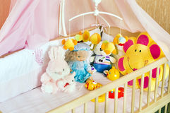 Various soft toys in the cot with orange linen Royalty Free Stock Photography