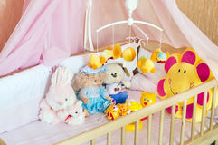 Various soft toys in the cot with orange linen Stock Image