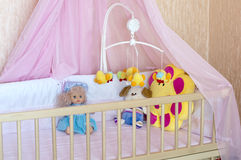 Various soft toys in the cot with orange linen Stock Photo