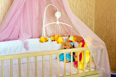 Various soft toys in the cot with orange linen Royalty Free Stock Photos