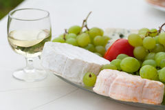 Various sorts of cheese. Grapes and glass of the white wine Stock Photos