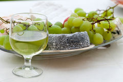 Various sorts of cheese. Grapes and glass of the white wine Stock Images