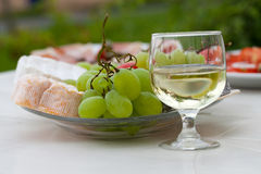 Various sorts of cheese,. Grapes and glass of the white wine Royalty Free Stock Photo