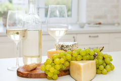 Various sorts of cheese, grapes and two glasses of the white win. E at the white clean cozy kitchen Stock Photos