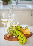 Various sorts of cheese, grapes and two glasses of the white win. E at the white clean cozy kitchen Royalty Free Stock Photography