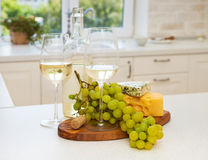Various sorts of cheese, grapes and two glasses of the white win. E at the white clean cozy kitchen Royalty Free Stock Image