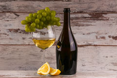 Various sorts of wine. Grapes and two glasses of the white wine Stock Photos