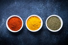Various spices in a bowls on stone table. Top view with copy space royalty free stock photo