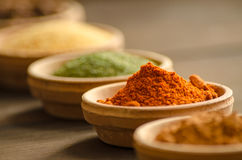 Various spices in ceramic bowls with selective focus on dried chilly. Low angle view - Shallow dept of field stock images