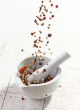 Various spices falling into mortar and pestle. On white wooden table Stock Image
