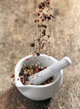 Various spices falling into mortar and pestle Royalty Free Stock Images