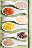 Various spices on green wooden table Stock Image