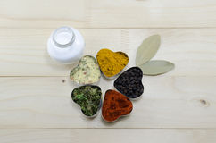 Various spices in heart chaped containers on a table Stock Image