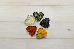 Various spices in heart chaped containers Royalty Free Stock Images