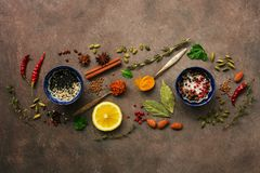 Various spices, herbs and seasonings on a brown rustic background. Top view, flat lay royalty free stock photos