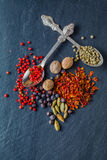 Various spices in old metal spoons on a stone background Stock Photos