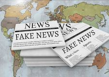 Fake news text on newspapers stacked over world map Royalty Free Stock Images