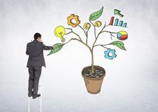 Man holding pen and Drawing of Business graphics on plant branches on wall. Digital composite of Man holding pen and Drawing of Business graphics on plant Royalty Free Stock Photo