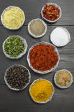 Various spices in shiny bowls on a dark wooden table Stock Images