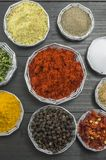 Various spices in shiny bowls on a dark wooden table Royalty Free Stock Photos