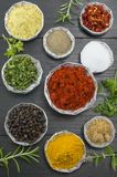 Various spices in shiny bowls on a dark wooden table Stock Photo