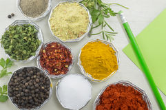 Various spices in shiny bowls with pen and paper for writing rec Royalty Free Stock Photo