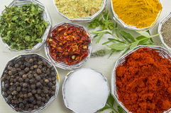 Various spices in shiny bowls on a white wooden table close up stock photography