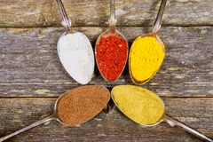 Various spices in silver spoons on old wooden table. Top view Royalty Free Stock Photo