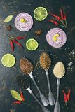 Various spices in spoons, coriander, sesame seeds, flax seed, peppercorns on a dark background. Slices of red onion and lime. View royalty free stock photos