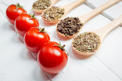 Various spices with tomato in wooden spoons Stock Photos