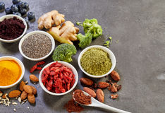 Various spices and vegetables. In white bowls, nuts and berries in studio shot from above over grey surface background Stock Image