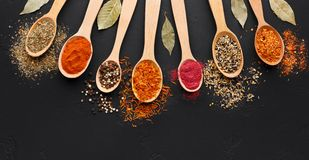 Various spices in wooden spoons on black background royalty free stock images
