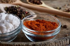 Various spices in wooden spoons and bowls and some salt on an old wooden barrel, top view, close-up, selective focus. Various spices in wooden spoons and bowls Stock Photos