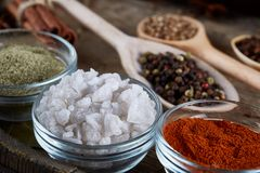 Various spices in wooden spoons and bowls and some salt on an old wooden barrel, top view, close-up, selective focus. Various spices in wooden spoons and bowls stock image