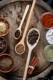 Various spices in wooden spoons and bowls and some salt on an old wooden barrel, top view, close-up, selective focus. Various spices in wooden spoons and bowls Stock Photo