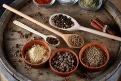 Various spices in wooden spoons and bowls and some salt on an old wooden barrel, top view, close-up, selective focus. Various spices in wooden spoons and bowls Royalty Free Stock Photo