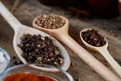 Various spices in wooden spoons and bowls and some salt on an old wooden barrel, top view, close-up, selective focus. Various spices in wooden spoons and bowls stock photography