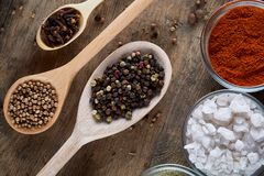 Various spices in wooden spoons and bowls and some salt on an old wooden barrel, top view, close-up, selective focus. Various spices in wooden spoons and bowls Stock Images
